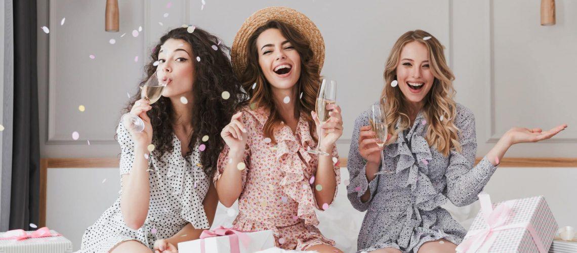 Image of caucasian stylish women 20s wearing dresses celebrating